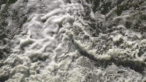 Turbulent vatten som forsar spurter på grunden av en fördämning arkivfilmer