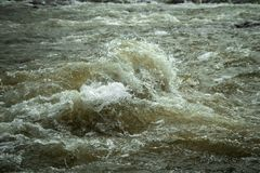 Turbulent water in river. Swollen due to snow melting stock image