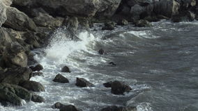 Turbulent water on a rocky coastline. With swirling eddies of white foam whipped up by the currents and tides stock video