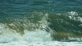 Turbulent water on a sandy coastline. With swirling eddies of white foam whipped up by the currents and tides stock footage