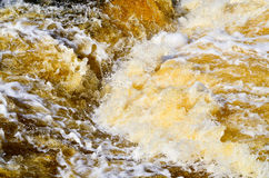 Turbulent Water. White water and foam churns over a small drop in a fast moving river Stock Images