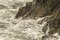 Turbulentes schäumendes Wasser, das herum wirbelt und oben auf eine felsige Felsspitze im Ozean - natürlich einfarbig spritzt stockfotos
