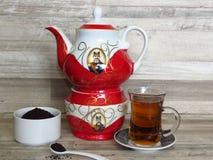 Turc, thé noir iranien et persan en verre Chai Théière iranienne rouge de porcelaine et poudre de thé noir dans une cuvette blanc images libres de droits
