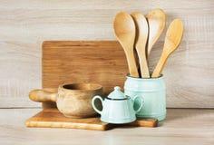 Turchese e terrecotte, stoviglie, utensili delle stoviglie e roba d'annata di legno su da tavolo di legno Natura morta della cuci immagini stock