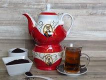 Turco, chá preto iraniano, persa no vidro Chai Pó do chá preto na bacia branca da porcelana dois Bule iraniano vermelho da porcel imagens de stock