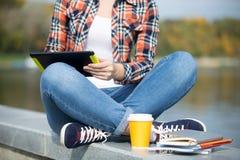 Turco que se sienta del estudiante en el puente con la tableta Imagen de archivo libre de regalías