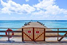 Turco, turcos e Caicos grandes - 3 de abril de 2014: Passeio à beira mar ao longo da praia do centro do cruzeiro fotografia de stock