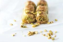 Turecki tradycyjny deserowy Baklava z pistacjami na białym pieczenie papierze, odosobnionym, zamyka w górę fotografia royalty free