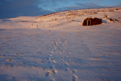 Turf house sunset #2. Tracks to turf house in snow as sun setting over Skjalfandi bay, near Husavik Iceland in April Royalty Free Stock Image