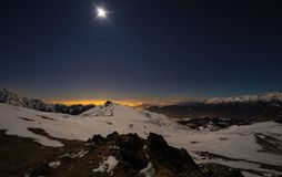 Turin city lights, night view from snow covered Alps by moonlight. Moon and Orion constellation, clear sky, fisheye lens. Italy. Turin city lights, night view Stock Image
