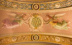 Turin - The detail of fresco of angels with initials of Virgin Mary on the ceiling in church Basilica Maria Ausiliatrice Royalty Free Stock Photo