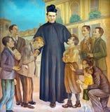 TURIN ITALIEN - MARS 15, 2017: Målningen av helgonet Don Bosco i mitt av hans pojkar i den kyrkliga basilikan Maria Ausiliatrice Arkivbild