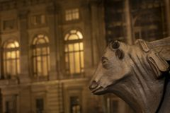 Turin, Piedmont, Italy: night view of bull head detail in the basement of a street lamp with in background Palazzo Madama in royalty free stock photography