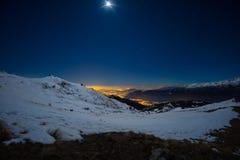Turin-Stadtlichter, Nachtansicht vom Schnee bedeckten Alpen durch Mondschein Mond- und Orions-Konstellation, klarer Himmel Italie lizenzfreie stockfotos