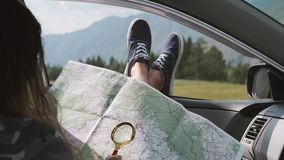 A turisk girl looks at a map using a magnifier while sitting in a car and sticking his legs out the window against the. Girl tourist looks at a road map using a stock footage