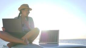 Turism flicka sitter på biltaket i panelljus talar på bärbara datorn och laddar upp den sol- samlingen, sammanträde för ung kvinn arkivfilmer