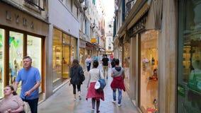 Turism och shopping, folkmassa av turister promenerar de smala gatorna nära souvenir shoppar arkivfilmer