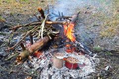 Turismo, cotos, gachas de avena en un tarro, calor en el fuego Imagen de archivo libre de regalías