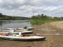 Turismo del río de los kajaks y de las paletas de la orilla Fotos de archivo