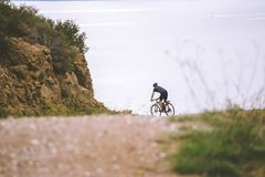Turismo del tema y ciclo en biking de la montaña individuo joven que monta abajo en la velocidad en rocoso, contexto S mediterrán Fotos de archivo libres de regalías