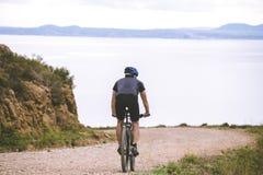 Turismo di tema e ciclare sul ciclismo di montagna giovane tipo che guida giù all'alta velocità su roccioso, il Mediterraneo S de Fotografia Stock