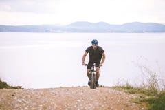 Turismo di tema e ciclare sul ciclismo di montagna il tipo guida in salita su una strada rocciosa e rocciosa contro lo sfondo del fotografie stock libere da diritti