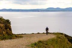 Turismo di tema e ciclare sul ciclismo di montagna il tipo guida in salita su una strada rocciosa e rocciosa contro lo sfondo del immagini stock libere da diritti