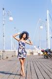 Turismo di viaggio e concetto della gente Giovane donna con il cappello che sta le barche vicine in porticciolo immagine stock libera da diritti