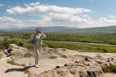 Turismo en las montañas de Georgia Mujer joven en una meseta de la montaña en un día soleado foto de archivo libre de regalías