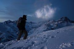 Turismo extremo El expeditor valiente enciende la manera con un faro en las montañas del invierno de la noche El hombre con la mo Fotografía de archivo libre de regalías