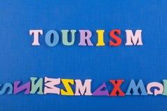TURISMord på blå bakgrund som komponeras från träbokstäver för färgrikt abc-alfabetkvarter, kopieringsutrymme för annonstext Arkivbild