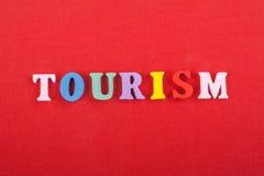 TURISMord på röd bakgrund som komponeras från träbokstäver för färgrikt abc-alfabetkvarter, kopieringsutrymme för annonstext Royaltyfria Foton