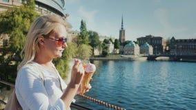 Turist- ätaglass för kvinna på bakgrunden av den igenkännliga sikten av staden av Stockholm i Sverige stock video