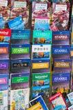 Turist- affischer och kartbokfotoalbum för turister av staden av den Istanbul besökareförsäljningen i en gata shoppar royaltyfria foton
