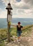 Turist- anseende för kvinna och förbise stolpen med information arkivfoto