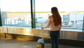Turist- anseende för lopp med hållande ögonen på solnedgång för bagage på flygplatsfönstret royaltyfria foton
