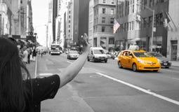 Turist- appell en gul taxi i Manhattan med typisk gest Arkivbild