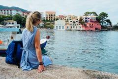 Turist- bärande blå klänning för kvinna som sitter på pir och ser till den pittoreska fjärden Assos by med härligt royaltyfria bilder