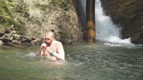 Turist- badning i sjön för stenigt berg som förnyar sig efter en lång vandring lager videofilmer
