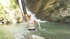 Turist- badning i sjön för stenigt berg som förnyar sig efter en lång vandring arkivfilmer
