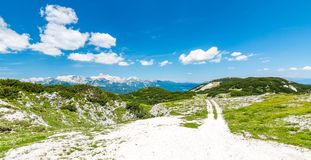 Turist- bana i Slovenien berg nära Vogel Bana av överkanten av berget, grönt gräs, lock, blå himmel fotvandra i Europa Triglav na Fotografering för Bildbyråer