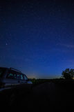 Turist- bil på stjärnklar bakgrundshimmel och Vintergatan Arkivbilder