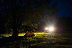 Turist- campa för natt Romantiska parturister har en vila på en lägereld nära det upplysta tältet under fantastisk natthimmel arkivbild