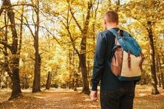 Turist eller handelsresande med en ryggsäck i höstskogen royaltyfri fotografi