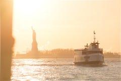Turist- färja och staty av frihet i den solbelysta New York hamnen Arkivbild