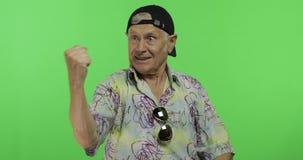 Turist för hög man i färgrik skjorta som firar känslomässigt gammal stilig man lager videofilmer