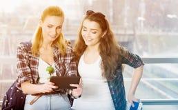 Turist för två unga kvinnor som använder den digitala minnestavlan Fotografering för Bildbyråer