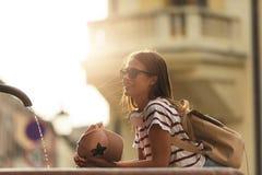 Turist för ung kvinna som förnyar vid den offentliga springbrunnen på en varm sommardag arkivbilder