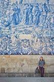 Turist för ung kvinna som går nära kyrkan med berömda portugisiska blåa keramiska tegelplattor på fasaden som reser i den Porto s arkivbilder