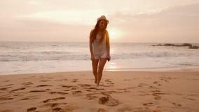 Turist för ung kvinna som promenerar havstranden på solnedgången arkivfilmer
